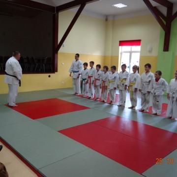 dzieci i ich trener na sali podczas treningu judo