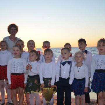grupa dzieci wraz z opiekunką pozują na tle morza