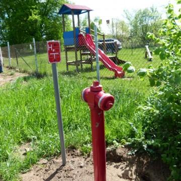 nowy hydrant na trawniku obok placu zabaw