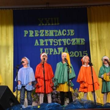 występ na scenie małych dzieci przebranych w kolorowe stroje krasnoludków