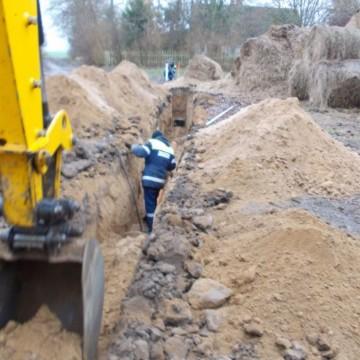 koparka oraz robotnik podczas robót przy budowie sieci kanalizacji sanitarnej  w Grąbkowie ETAP II